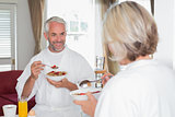 Mature man having breakfast with cropped woman at home
