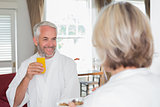 Smiling mature man having breakfast with cropped woman