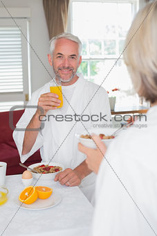 Mature man having breakfast with cropped woman
