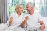 Mature couple with coffee cups sitting on bed