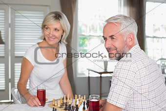 Mature couple looking away while playing chess