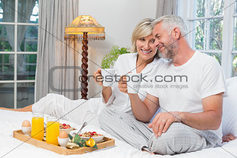 Smiling mature couple with coffee cups sitting on bed