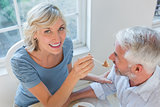 Smiling woman feeding mature man pastry