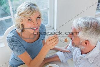 Smiling woman feeding mature man pastry