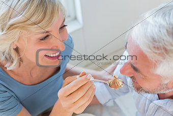 Close-up of a smiling woman feeding mature man pastry