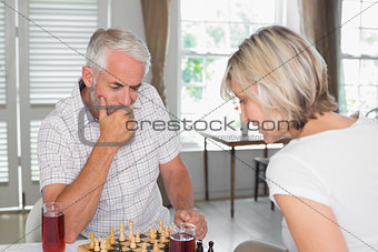 Serious mature couple playing chess at home