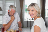 Happy mature couple playing chess at home