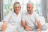 Smiling mature couple sitting on bed at home