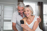 Couple reading text message at home