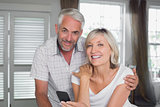 Happy mature couple reading text message at home