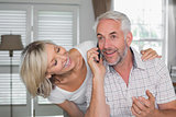 Woman with mature man while he's using mobile phone