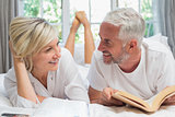 Happy mature couple reading book in bed