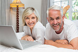 Portrait of a mature couple using laptop in bed