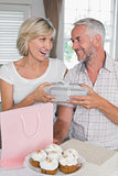 Mature man giving a gift box to happy woman