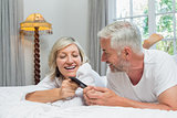 Cheerful mature couple reading text message