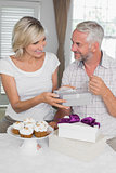 Happy woman giving a gift box to mature man