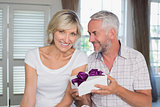Happy mature couple with a gift box at home