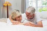 Happy mature couple lying in bed at home