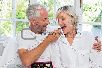 Mature man feeding woman chocolates