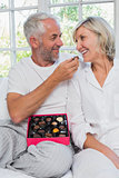 Loving mature man feeding woman chocolates