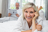 Smiling woman with man reading newspaper in bed