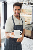 Smiling waiter holding coffee cup at café