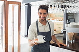 Waiter holding cup of coffee at café