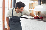 Waiter cleaning countertop with sponge