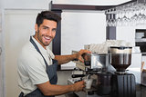Smiling waiter making cup of coffee at coffee shop