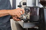 Mid section of a barista prepares espresso in coffees hop