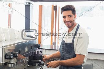 Smiling barista preparing espresso at coffee shop