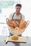 Happy young waiter with basket of breads at coffee shop counter
