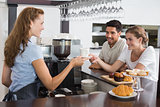 Female waiter giving coffee to a couple at coffee shop