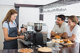 Couple looking at waitress prepare coffee at coffee shop