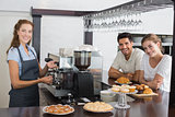 Smiling couple with female cafe owner at coffee shop