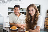 Smiling couple with coffee and croissant at coffee shop