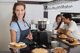 Smiling cafe owner holding sweet snacks with couple at counter in coffee shop
