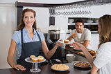 Female cafe owner with sweet snacks and couple at counter in coffee shop