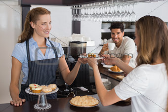 Cafe owner giving sweet food to a couple at coffee shop