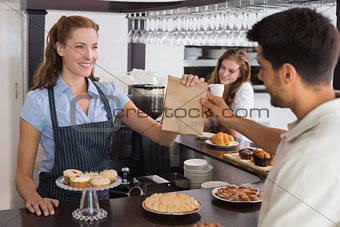 Cafe owner giving packed food to a couple at coffee shop