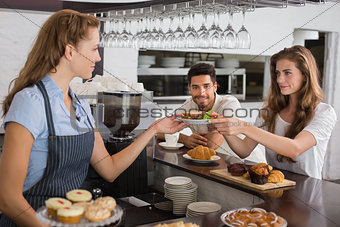 Cafe owner giving sandwich to a woman at coffee shop