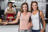 Female friends with male barista at counter in coffee shop