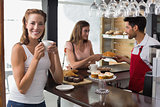 Woman drinking coffee with friend and male barista in coffee shop
