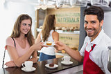 Barista giving pastry to woman at counter in coffee shop