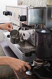 Mid section of a barista prepares espresso in coffee shop