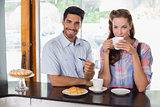Smiling couple with man holding credit card at coffee shop