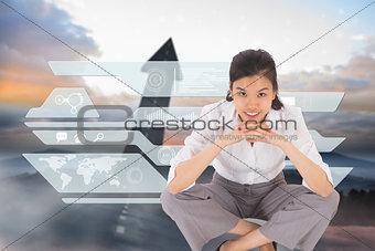 Composite image of smiling businesswoman sitting cross legged