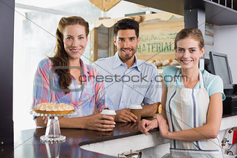 Smiling barista with a couple at counter in coffee shop