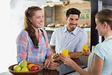 Waitress giving orange juice to a couple at coffee shop