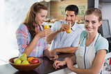 Waitress with couple drinking orange juice at coffee shop